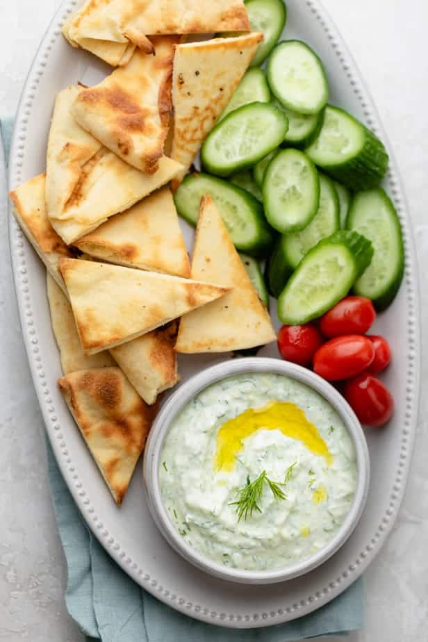 Tzatziki sauce recipe on a platter with pita and vegetables