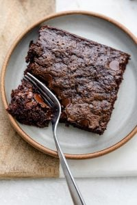 Zucchini brownie square on a plate with fork cutting into one