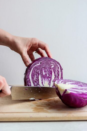 Tutorial for how to cut cabbage, showing cabbage sliced in half