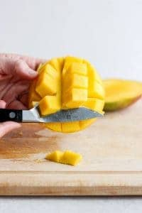 Illustrating the knife method for removing the mango from the skin