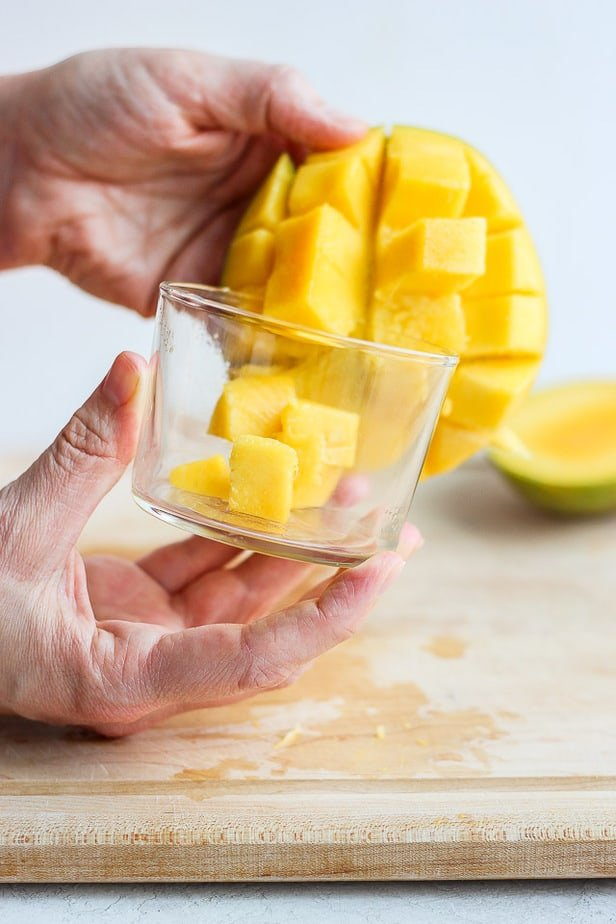 placing cut mango cubes into glass