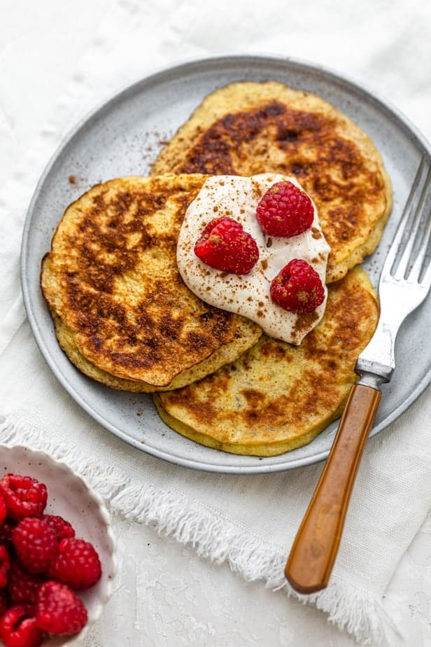 3 Ingredient Pancakes on a plate topped with yogurt and raspberries