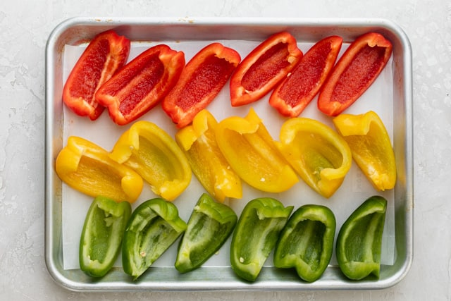Slices of bell pepper on a baking sheet