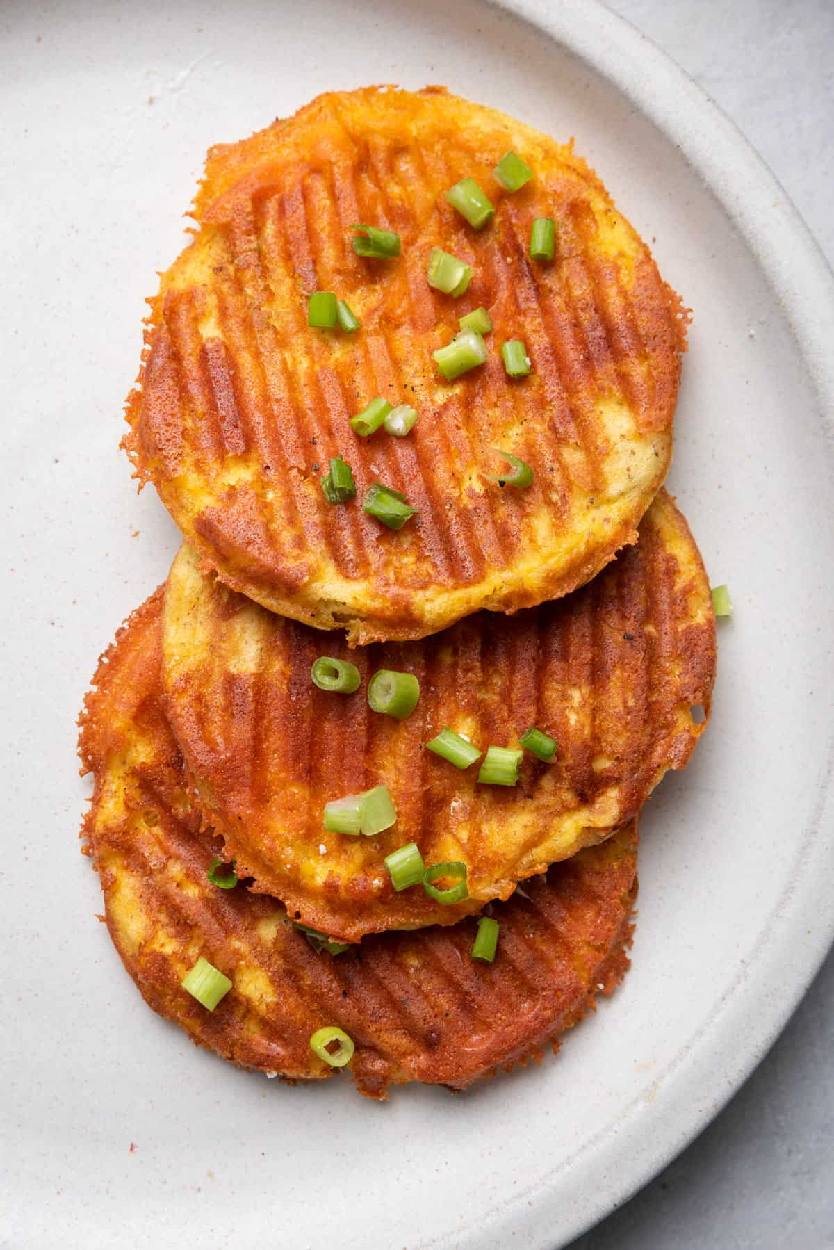 3 stacked chaffles on top of each other on a plate garnished with green onions