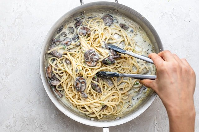 hand with tongs mixing a pot of creamy mushroom pasta