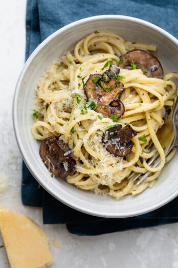 Creamy garlic mushroom pasta in a bowl with parmesan cheese next to it
