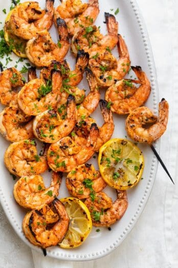 Grilled shrimp skewers on a white plate with grilled lemon slices