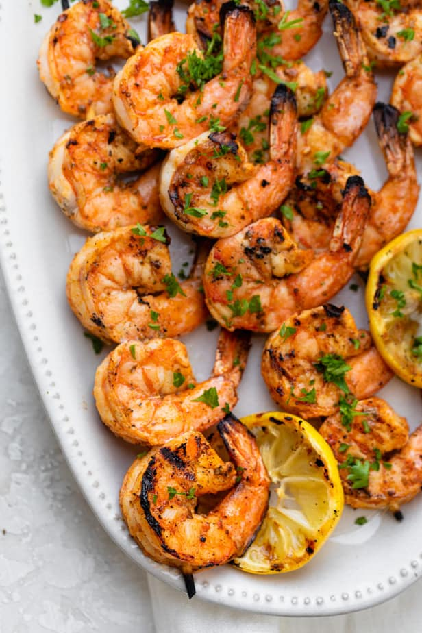 Grilled Shrimp Skewers served on a white plate with lemon slices