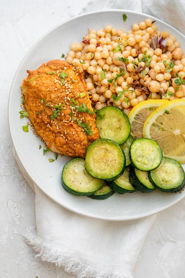 Hummus crusted chicken on a plate with zucchini slices and couscous