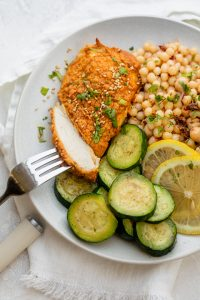 Hummus crusted chicken being cut with a fork