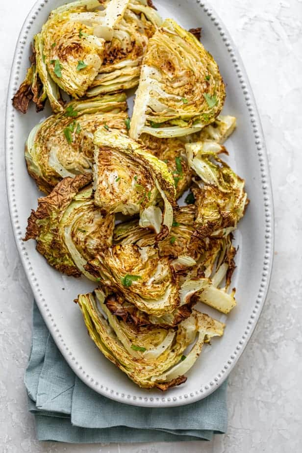 Roasted cabbage wedges served in a white plate