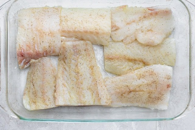 Seasoning cod fillet with salt and pepper before frying