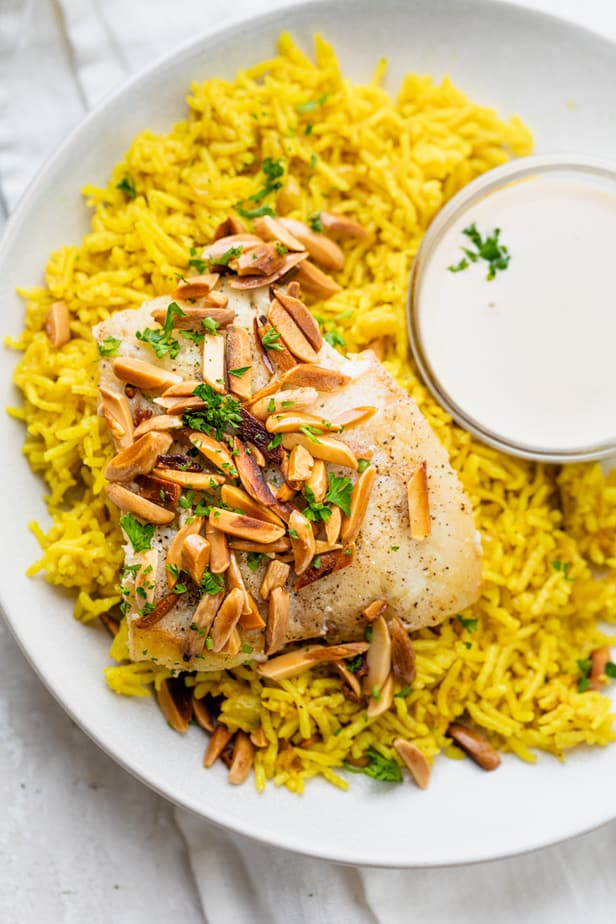 One plate serving of sayadieh - lebanese rice and fish served with tahini sauce to pour on top