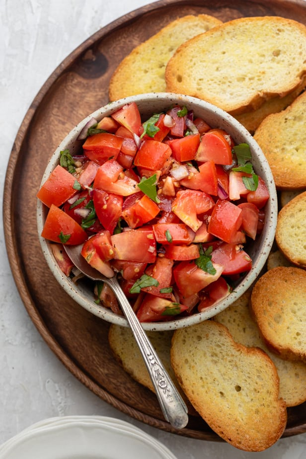Tomato bruschetta in a bowl being served with toast on the side