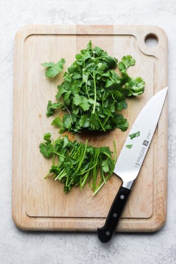 cilantro with ends cut off on a wooden chopping board