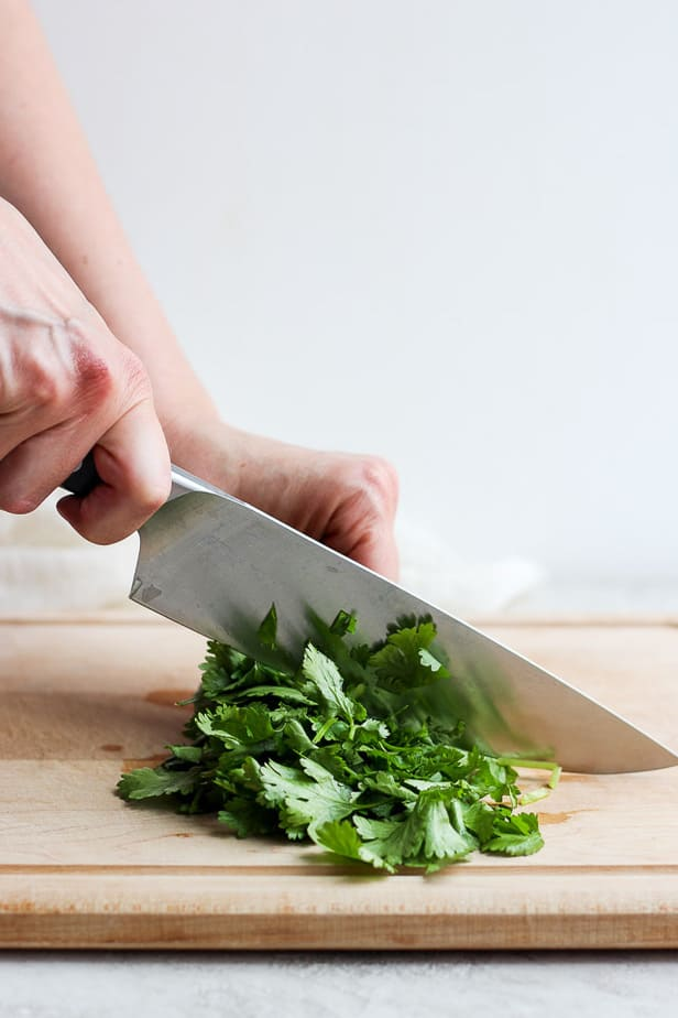chopping cilantro on a wooden chopping board