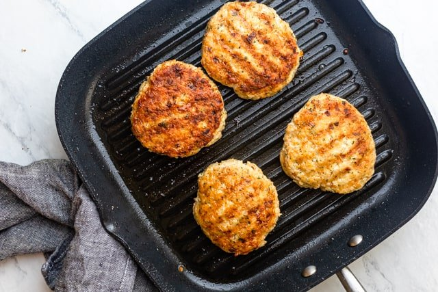 4 chicken patties after grilling resting on grill pan