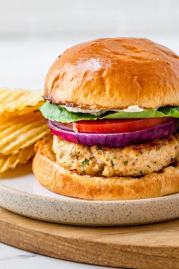 Up close shot of a ground chicken burger in bun with lettuce, tomatoes and onions