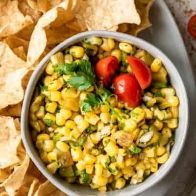 Close up shot of bowl of corn salsa with chips around the bowl