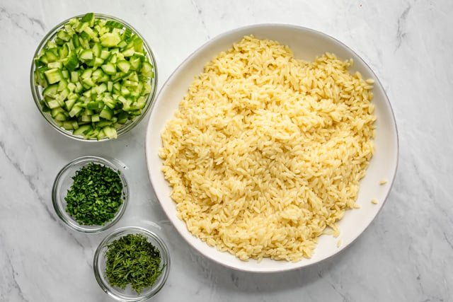 Orzo salad tossed in the dressing in a large bowl with cucumbers and herbs on the side