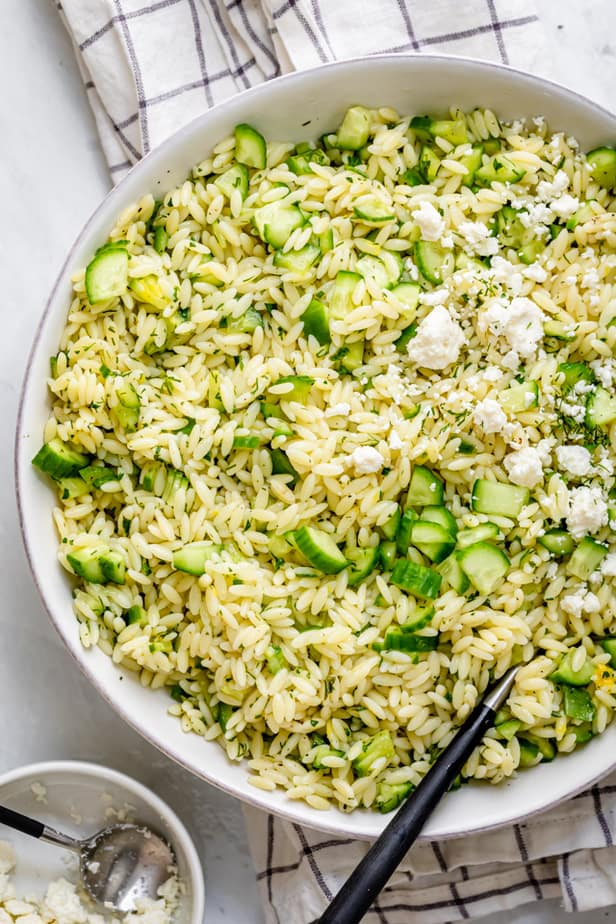 Cucumber lemon orzo salad topped with feta cheese with small bowl of feta on the side