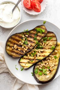 Grilled eggplant on a plate topped with pinenuts