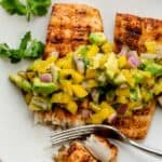 Cutting off mahi mahi fillet with mango avocado salsa on top
