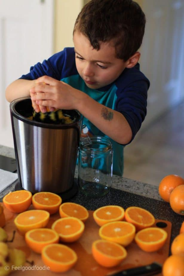 My son juicing oranges with a small citrus juicer