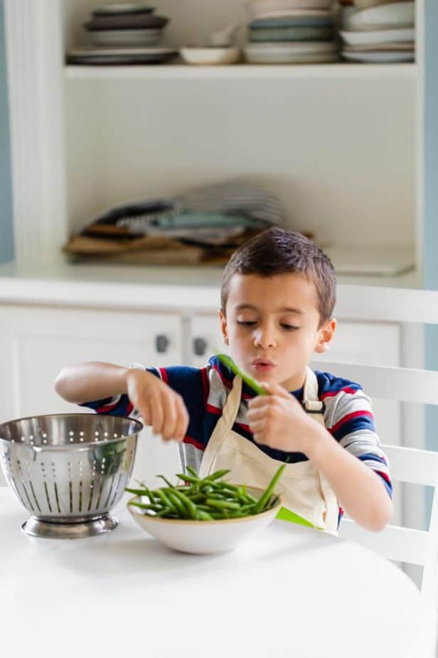 My son with bowl of green beans trimming off ends