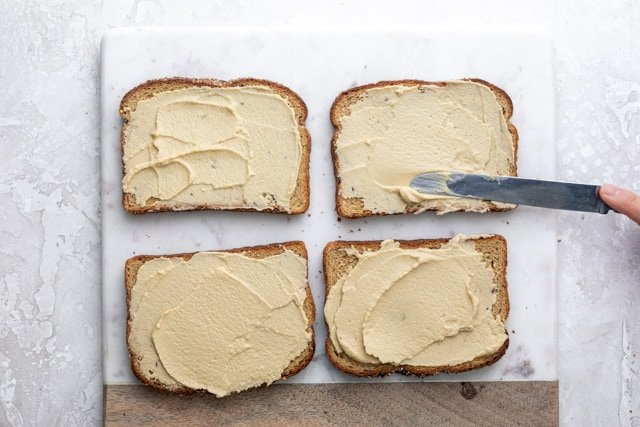 Spreading hummus on four slices of bread