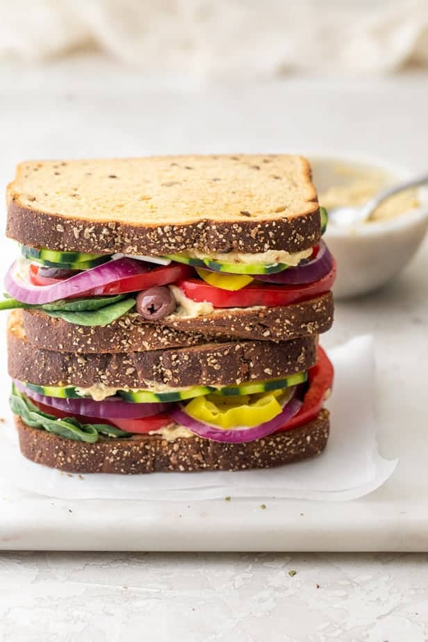 Veggie and hummus sandwiches stacked on top of each other with small bowl of hummus in background