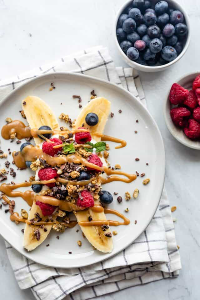 Healthy banana split topped with yogurt, fruit and granola