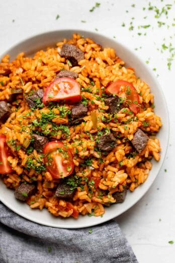 Jollof rice served in a bowl with beef and tomatoes on top