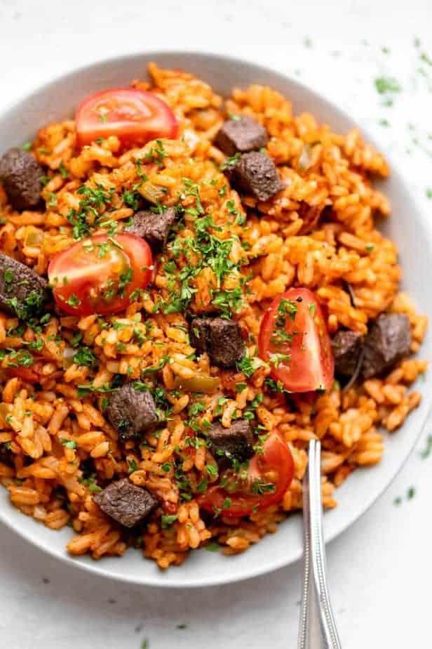 Spoon in bowl of Nigerian jollof rice