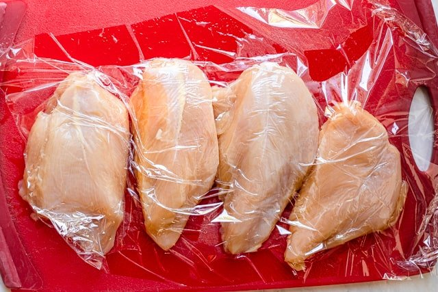 Chicken on red cutting board covered in plastic wrap before pounding