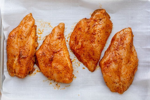 Marinated chicken on baking sheet lined with parchment paper