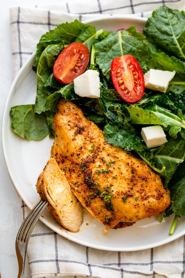 Chicken breast on plate cut up with salad