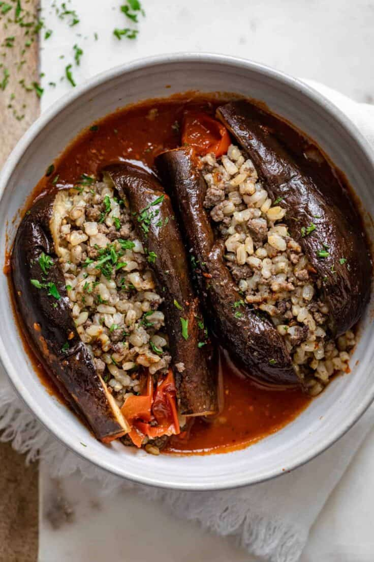 Final cooked stuffed eggplant cut in half to show the rice and beef stuffing