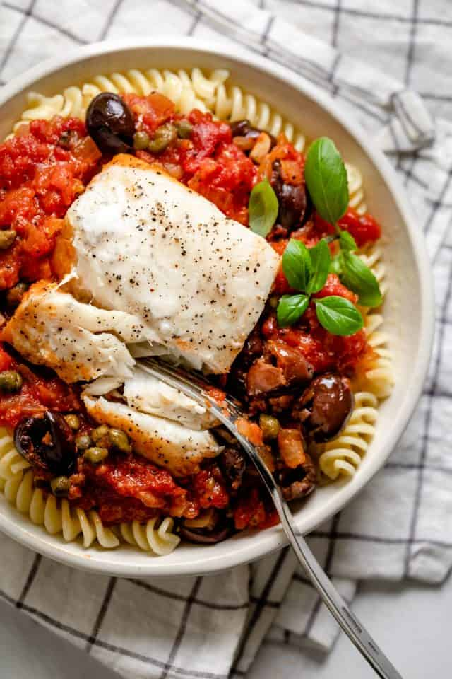 Piece of the poached fish served over the tomato sauce along with pasta in a small white bowl