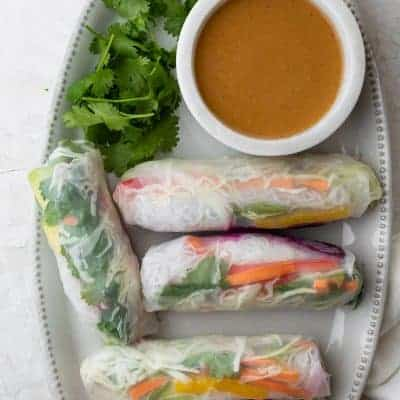Platter of Vietnamese vegetable spring rolls with peanut dipping sauce