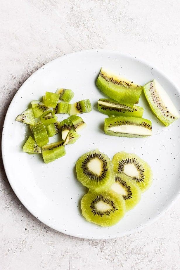 Kiwi cut three ways on a plate