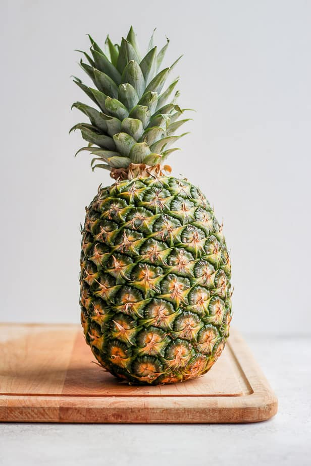 Large uncut pineapple on a cutting board