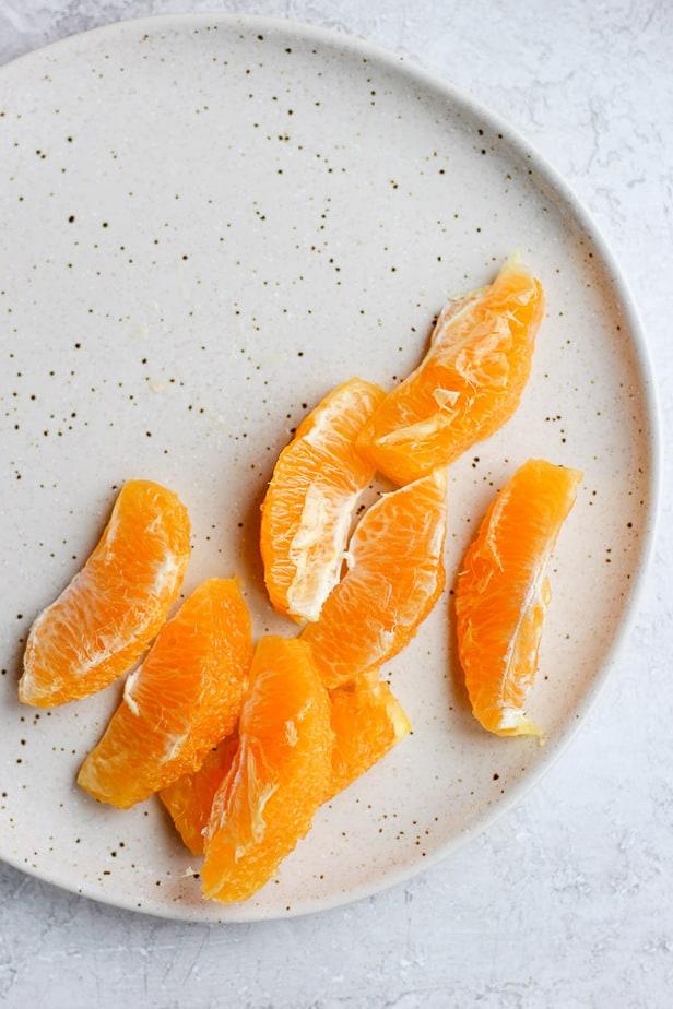 Segmented orange slices on a white plate