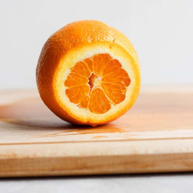 Orange on cutting board with the top sliced off