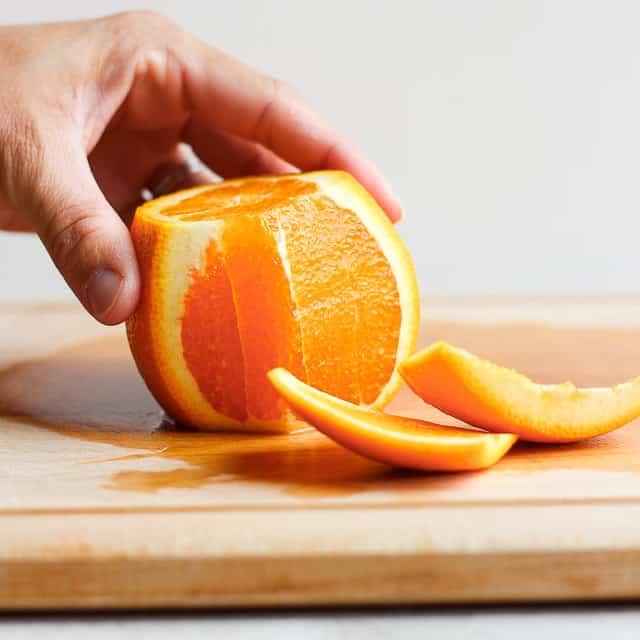 Orange on cutting board with peel removed