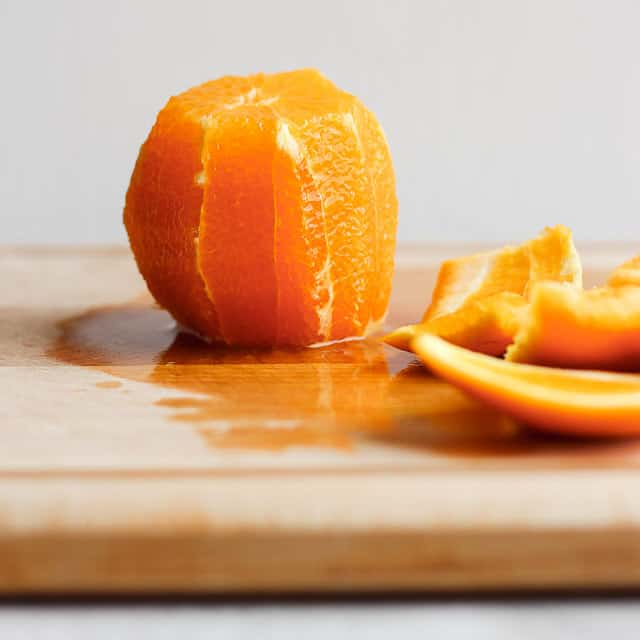 Peeled orange on cutting board with peels on the side