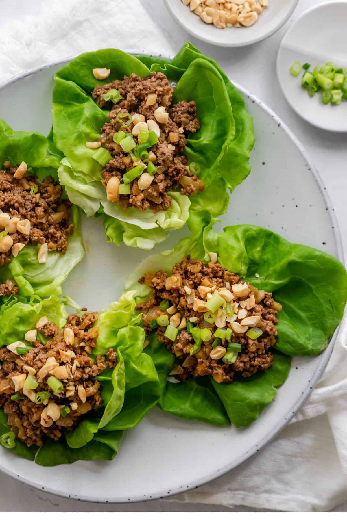 Round plate with four butter lettuce pieces topped with the ground beef mixture