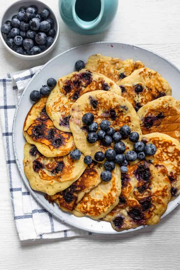 Round plate of 12 pancakes topped with blueberries with a side of maple syrup