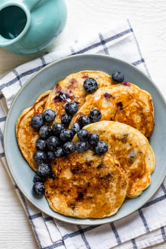 Plate of blueberry pancakes served with maple syrup