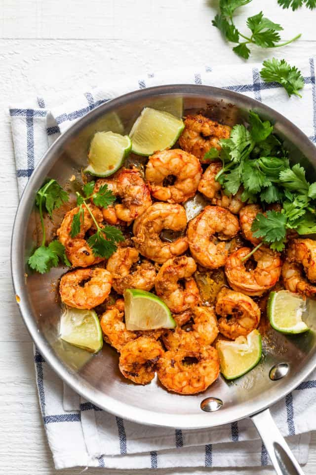 Chili lime shrimp in a saute pan with cilantro and lime wedges